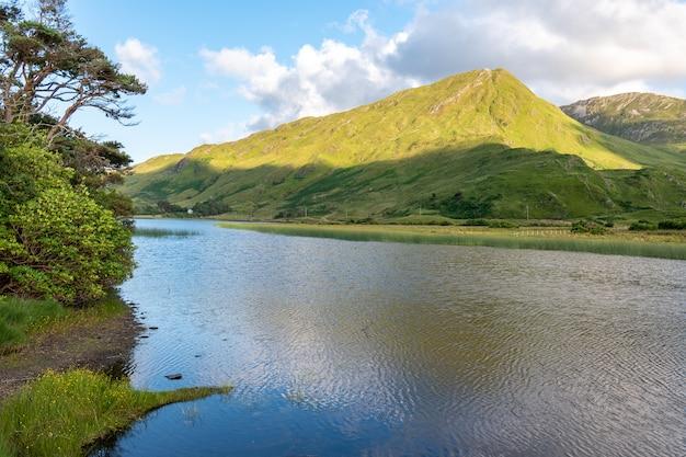 View over pollacapall lake to green mountain, connemara national park, ireland