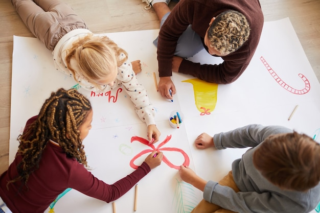 Above view portrait of female teacher sitting on floor with multi-ethnic group of kids drawing pictures while enjoying art class, copy space
