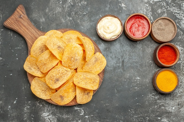 Above view of potato chips spices and mayonnaise with ketchup on wooden cutting board on gray table