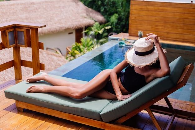 Vista della donna abbastanza abbronzata in bikini vintage nero si trova sul lettino verde in splendida villa al giorno pieno di sole, riposando, godendo le vacanze