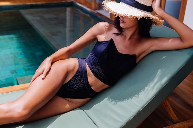View of pretty tanned woman in black vintage bikini lies on green sun bed at amazing villa at sunny day, resting, enjoying vacation