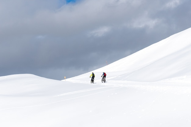 View of professional cyclists riding bicycles in scenic snow-covered mountains