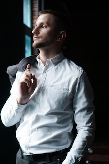 View in profile of a young businessman, dressed in a white shirt standing near the window on a dark walls