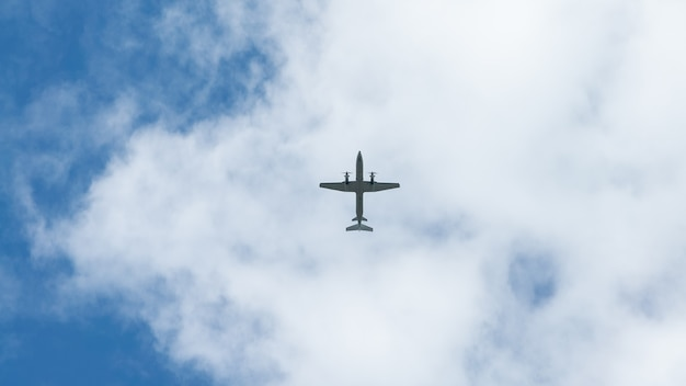 View of propeller plane fly low with blue sky and clouds at background. commercial passenger aircraft across flying over head. plane in the air. flight trip