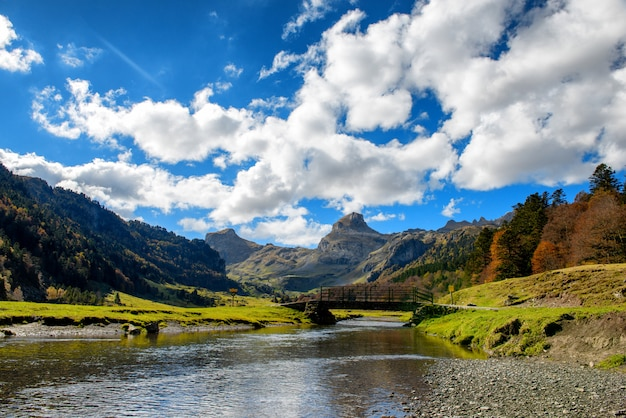 View of pyrenees mountains with small river near pic ossau