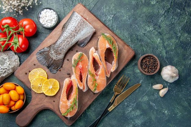 Sopra la vista di pesce crudo fette di limone verdi pepe sul tagliere di legno posate di pomodori impostato sul tavolo scuro