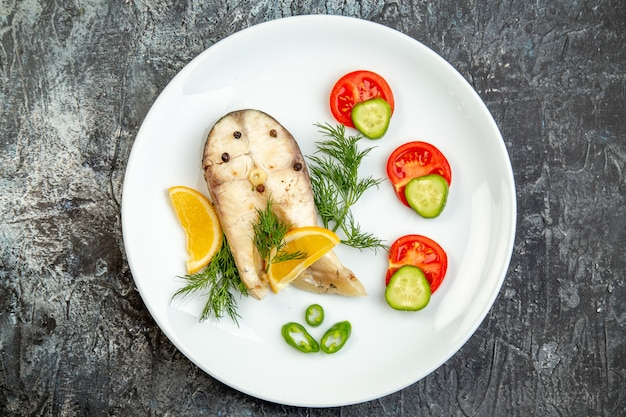 Sopra la vista dei pesci crudi e degli alimenti freschi del pepe sul piatto bianco sulla superficie grigia del ghiaccio con spazio libero