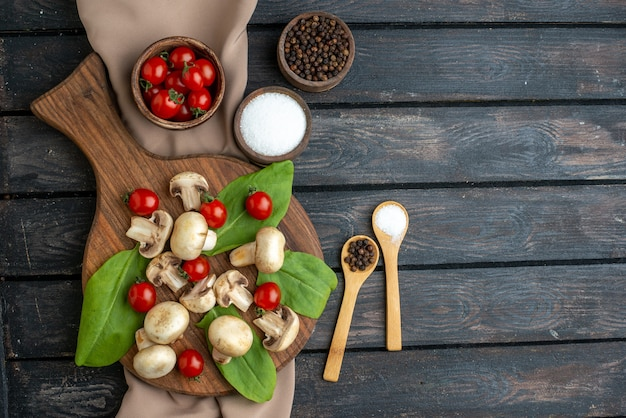 Above view of raw fresh mushrooms and tomatoes peppers spices on wooden board towel on black background