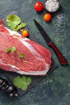 Sopra la vista di carne rossa fresca cruda e verdure sul tagliere coltello pomodori martello di legno su sfondo nero verde colori misti