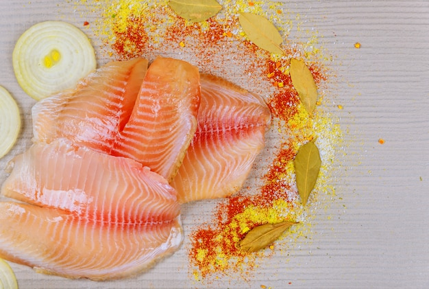 Above view of raw fresh tilapia fillets over on cutting board