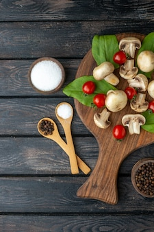 Above view of raw mushrooms and tomatoes spices on wooden board towel on black background