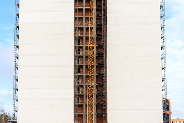 View of the rear facade of a block of flats under construction with a crane