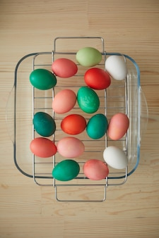 Above view of red and green hand-painted easter eggs on drying rack over wooden table in art studio, copy space