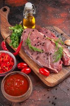 Sopra la vista di carne rossa su tagliere di legno e bottiglia di olio caduta pepe verde tritato all'aglio su sfondo scuro