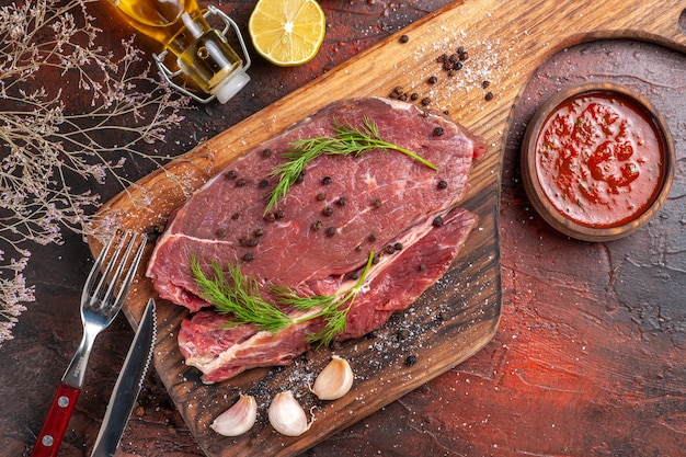 Above view of red meat on wooden cutting board and garlic green fork and knife fallen oil bottle and ketchup on dark background