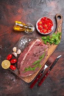 Sopra la vista della carne rossa sul tagliere di legno e della bottiglia di olio caduta del pomodoro del pepe tritato del limone verde dell'aglio su fondo scuro