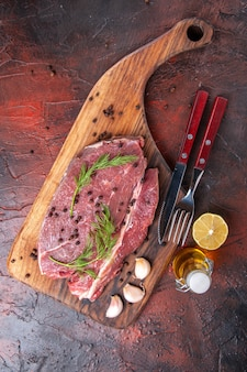 Sopra la vista di carne rossa sul tagliere di legno e forchetta e coltello della bottiglia dell'olio del pepe verde dell'aglio su fondo scuro