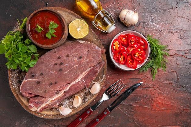 Sopra la vista di carne rossa su vassoio di legno e ketchup verde all'aglio e bottiglia di olio di pepe tritato su sfondo scuro