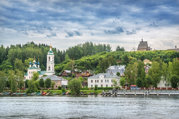View of residential buildings on the embankment, the varvara church and the church of peter and paul on mount levitan in the city of plyos (ivanovo region) from the volga river on a summer cloudy day