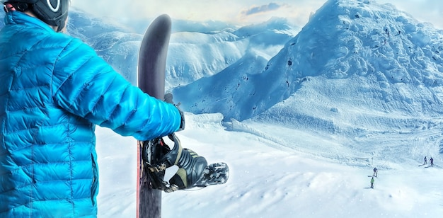 View of rider with snowboard standing in the mountains