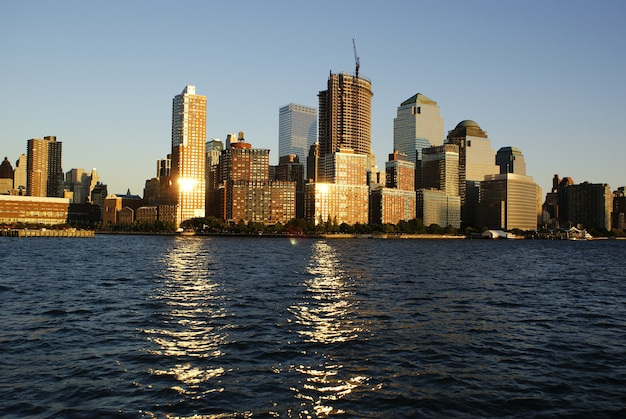 View of riverside park next to the city skyline at sunset from the hudson river.