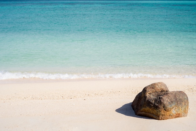 The view of a rock on the tropical beach at lipe thailand island with white sand,  turquoise ocean water and blue sky