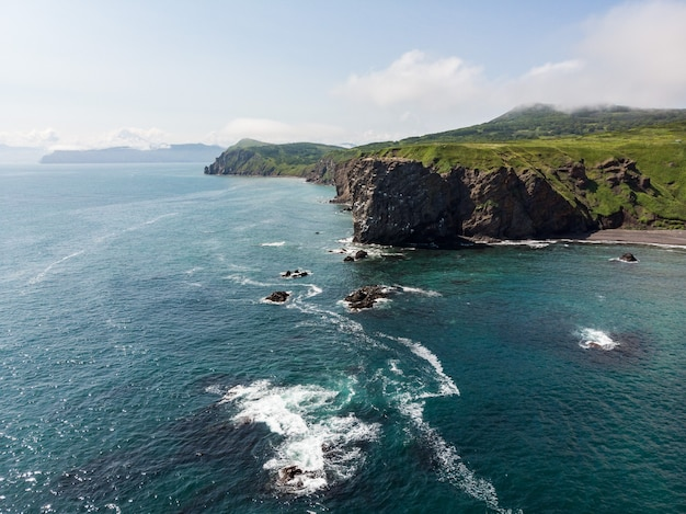 A view of the rocky coast of kamchatka from the side of the clear blue ocean Premium Photo