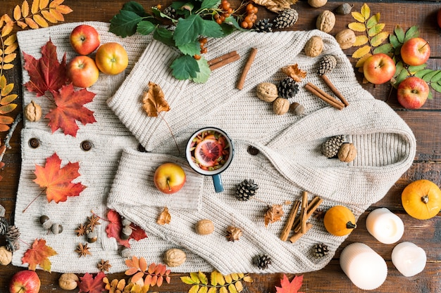 View of romantic autumn composition of ripe fruits, leaves, spices, hot tea, candles, nuts and cones on woolen sweater