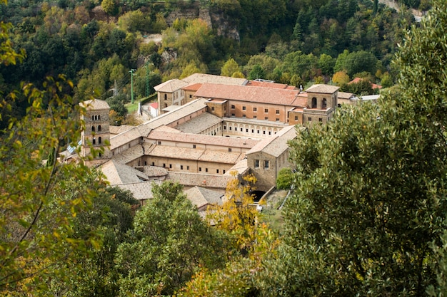 View of saint scholastica medieval monastery surrounded, by trees in subiaco. founded by benedict of nursia