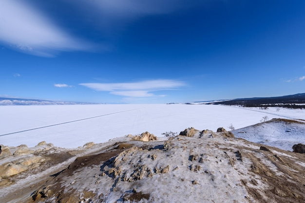 View to sarai beach from cape burhan on olkhon island on sunny winter day. frozen lake baikal covered with snow. beautiful stratus clouds over the ice surface on a frosty day.