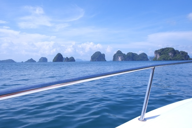 View sea from speed boat with mountains on blue sky background.