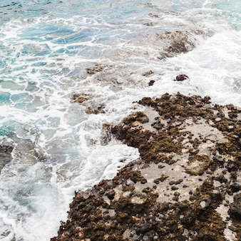 Above view sea touching rocky shore