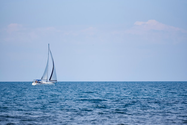 A view of the sea, a white yacht with sails and the sky.