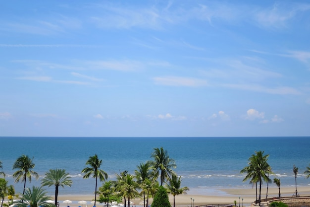 View of the sea with the coconut trees, blue sky and white clouds in summer time.