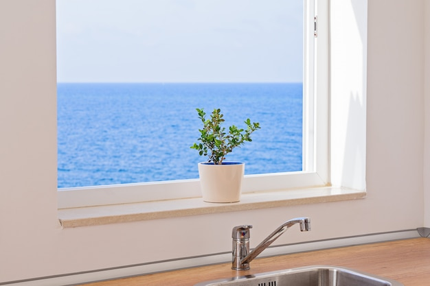 View of seascape through an open window in kitchen