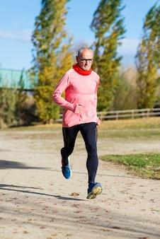 View of senior man jogging through parkv