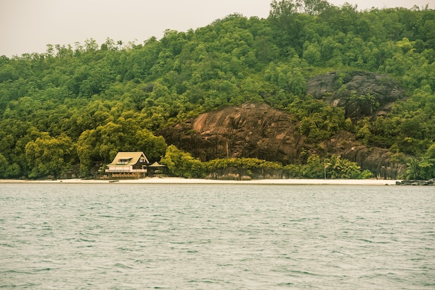 View of seychelles coastline with a house in the forest.