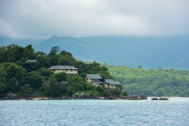 View of seychelles coastline with houses in the forest