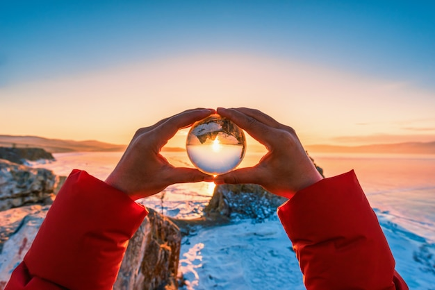 View of shamanka rock through a glass ball at sunset with natural breaking ice in frozen water on lake baikal, siberia, russia.