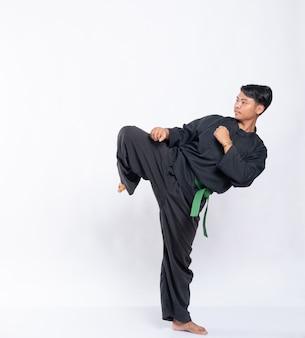 白地に緑のベルトが付いたプンチャック・シラットのユニフォームを着て片足を上げた男の側面を見る