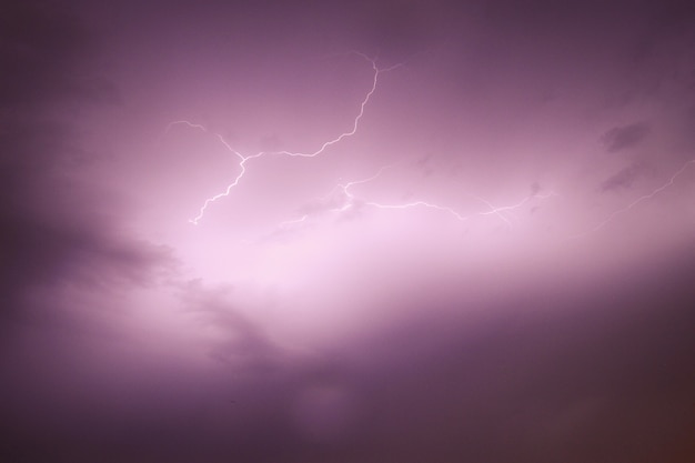 View of the sky capturing a bolt of lightning with purple cloudy skies