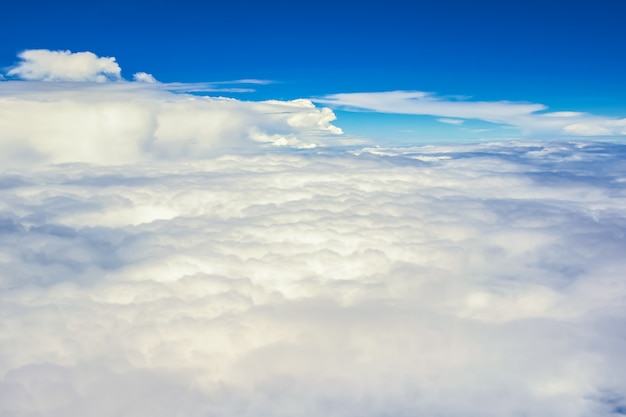View of the sky clouds above the clouds from airplane window