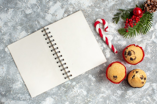 Above view of small cupcakes candy and fir branches decoration accessories conifer cone and notebookon ice surface