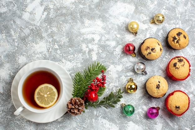 Sopra la vista di piccoli cupcakes e accessori decorativi rami di abete cono di conifere una tazza di tè nero sulla superficie del ghiaccio ice