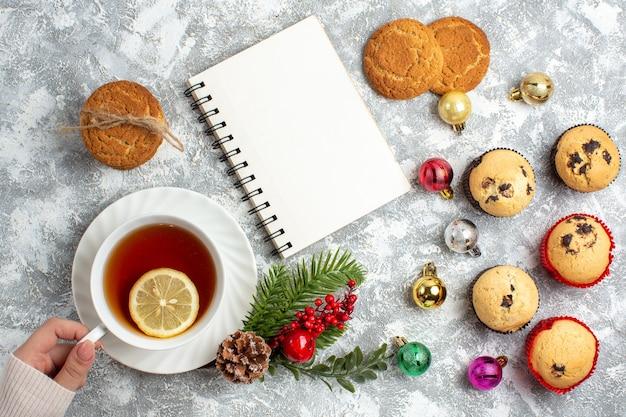 Sopra la vista di piccoli cupcakes e accessori decorativi rami di abete cono di conifere mano che tiene una tazza di tè nero torte impilate accanto al taccuino chiuso sulla superficie del ghiaccio
