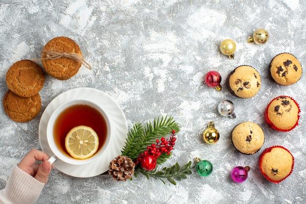 Sopra la vista di piccoli cupcakes e accessori per la decorazione rami di abete cono di conifere mano che tiene una tazza di tè nero torte impilate sulla superficie del ghiaccio