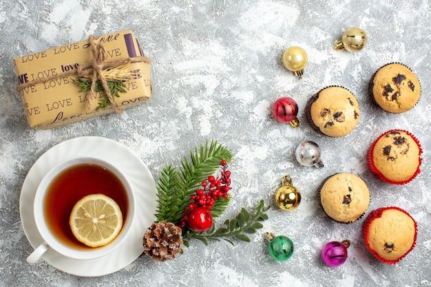Sopra la vista di piccoli cupcakes e accessori per la decorazione regalo rami di abete cono di conifere una tazza di tè nero sulla superficie del ghiaccio