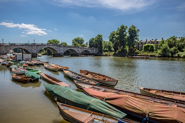 View of small wooden boats in the thames river near an old bridge