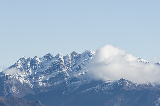 View of a snow-covered rocky mountain partially covered with clouds