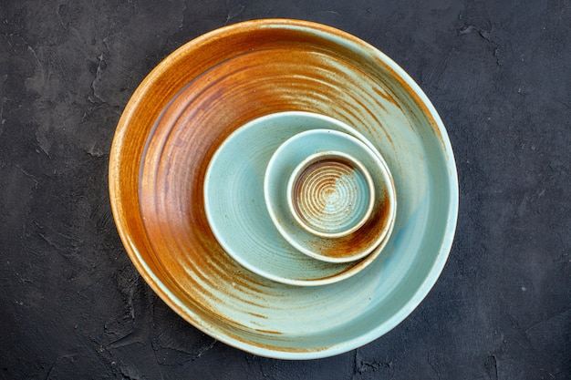 Above view of soft blue and brown color round plates on black background with free space
